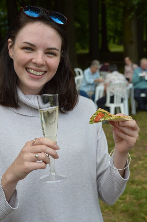 Woman holding pizza and prosecco at St Fagans Food Festival