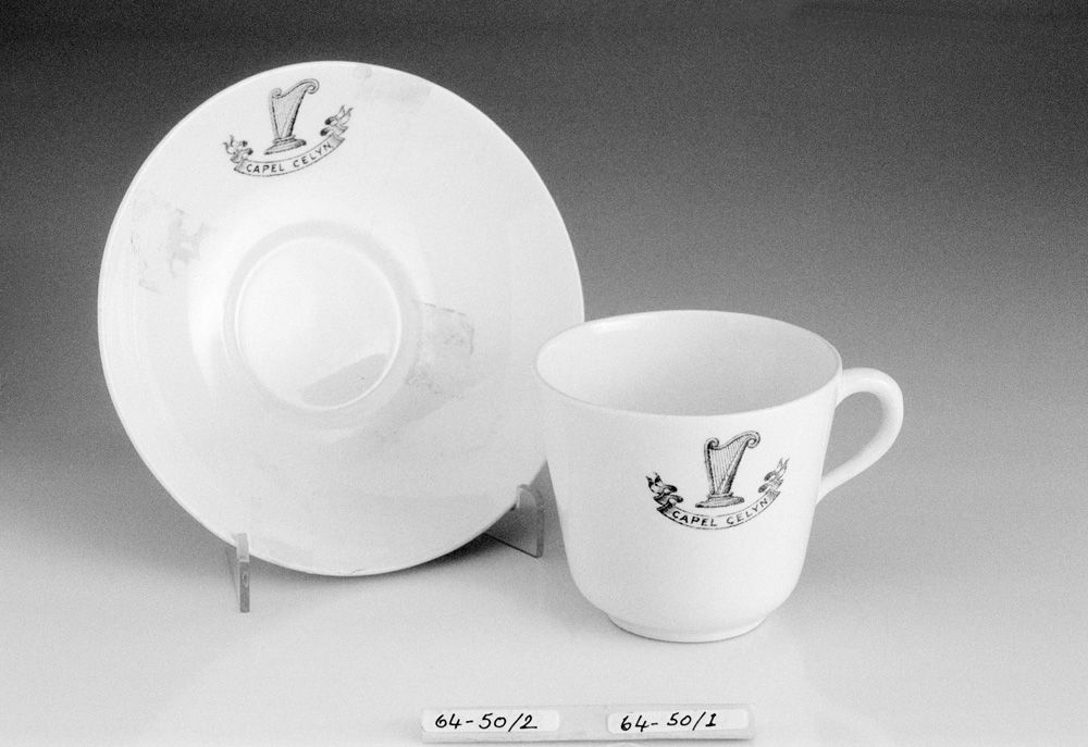 Photograph showing a cup and saucer with 'Capel Celyn' and a ribbon scroll design