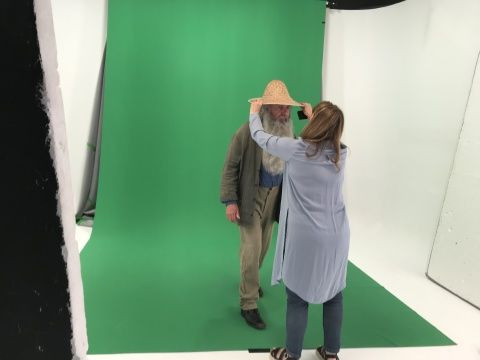 Actor dressed as the artist Monet standing in front of a green screen having his hat adjusted by a make up artist
