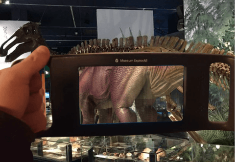 a device held up to a dinosaur skeleton showing augmented reality of the dinosaurs skin.
