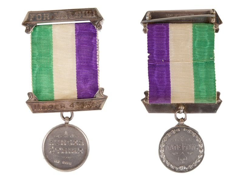 photo showing medal on a purple, white and green ribbon, which reads 'Hunger Strike' on the front, and 'Kate Evans' on the back