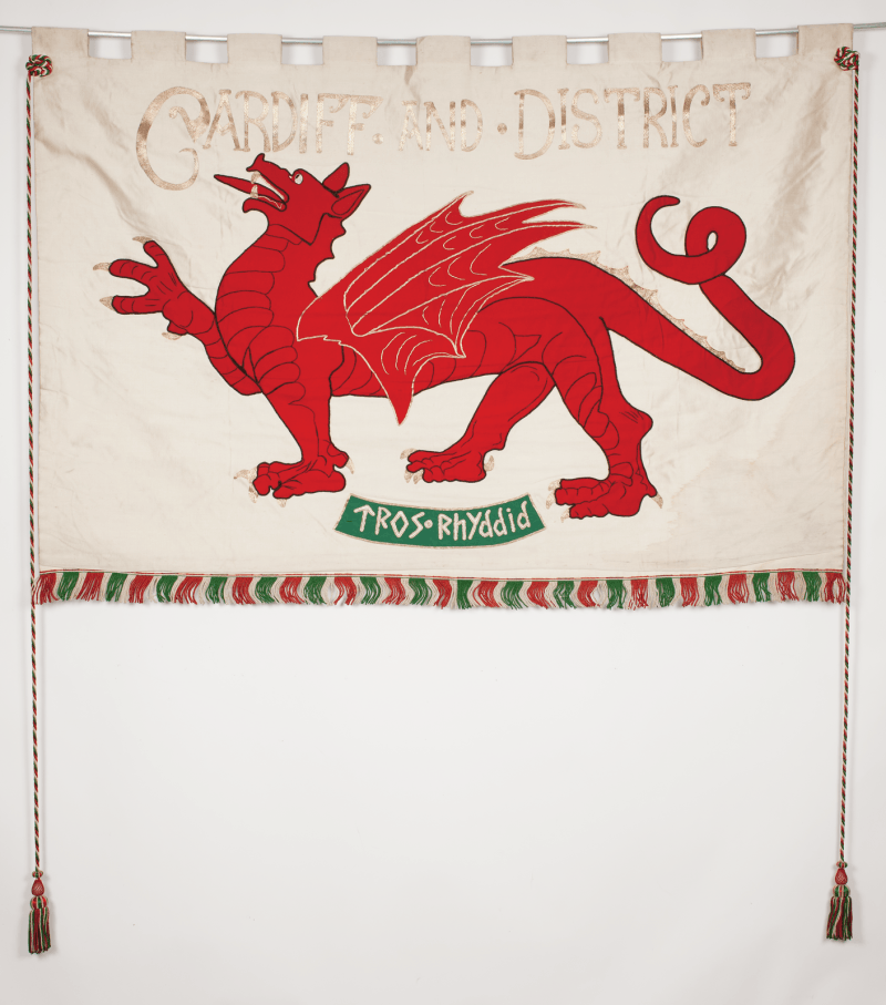 photo of embroided banner with a red dragon and the words 'cardiff and district' and 'tros rhyddid'