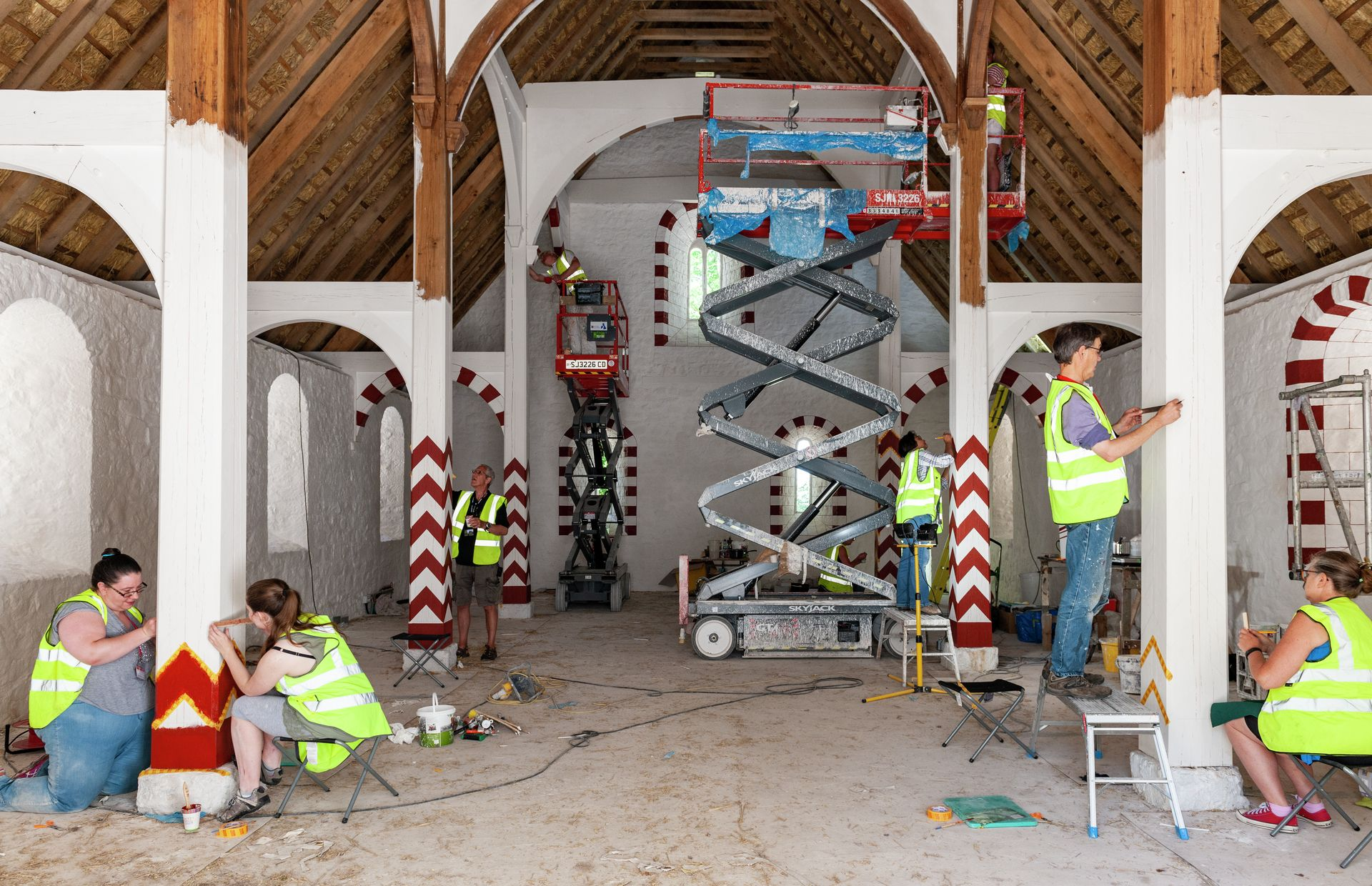 View of the hall showing several people at work painting the interior of the Llys.
