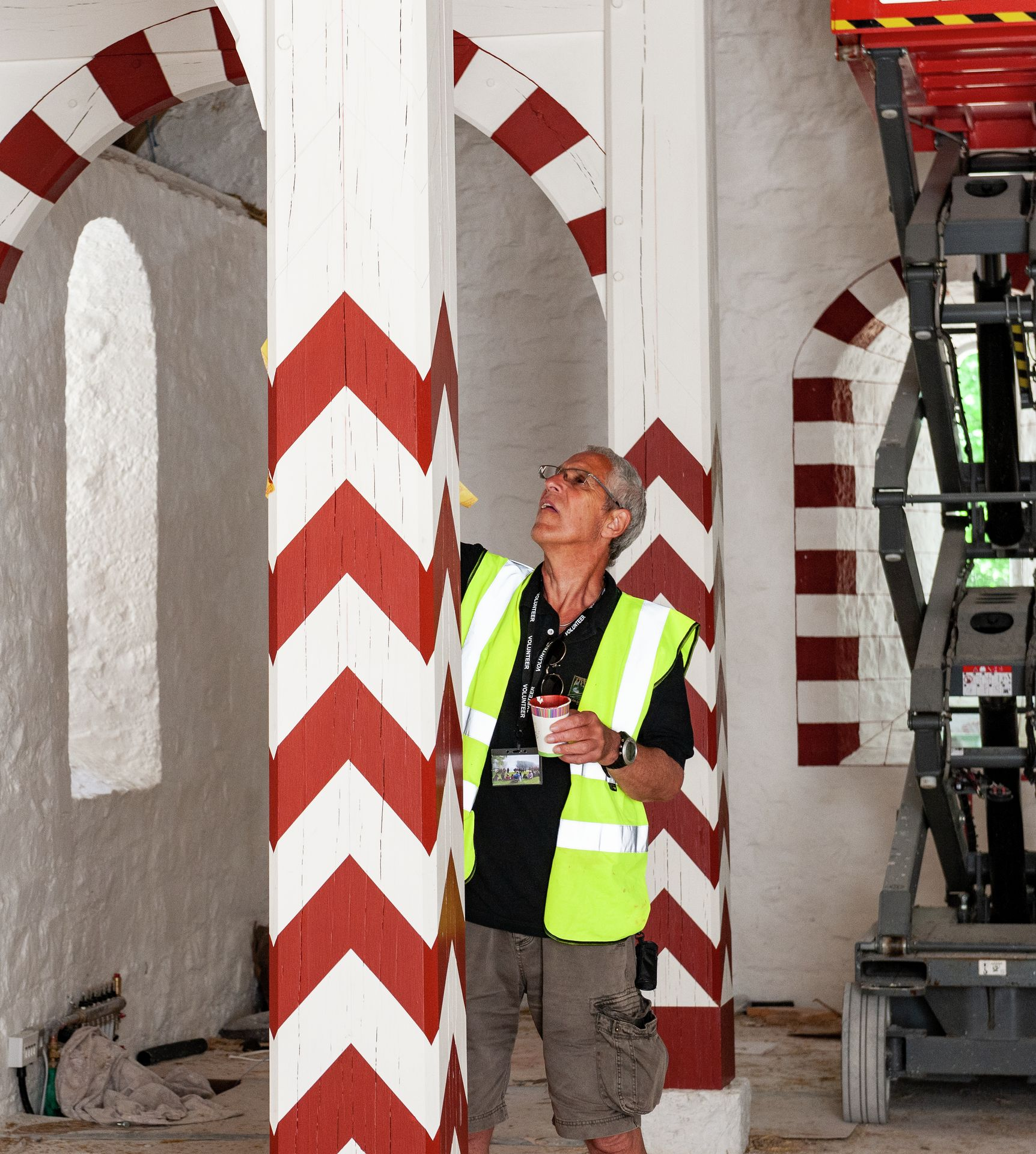 Volunteer decorating wooden posts by painting large red chevrons onto a white background.