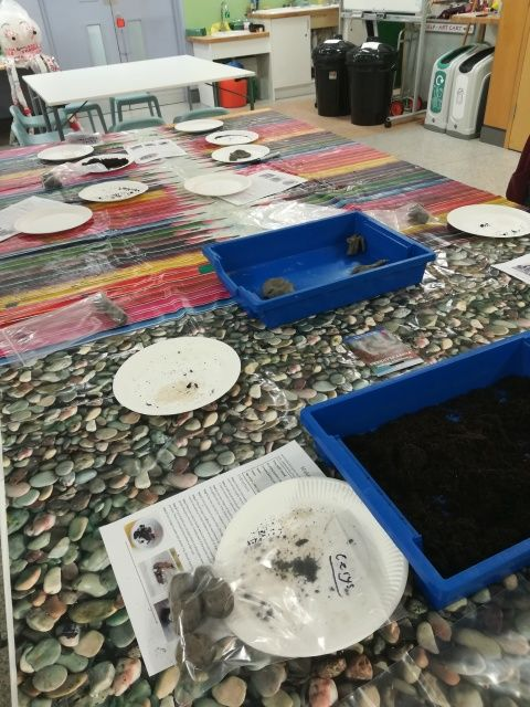 Photograph of tabletop with containers of clay and soil, where visitors were making seed bombs