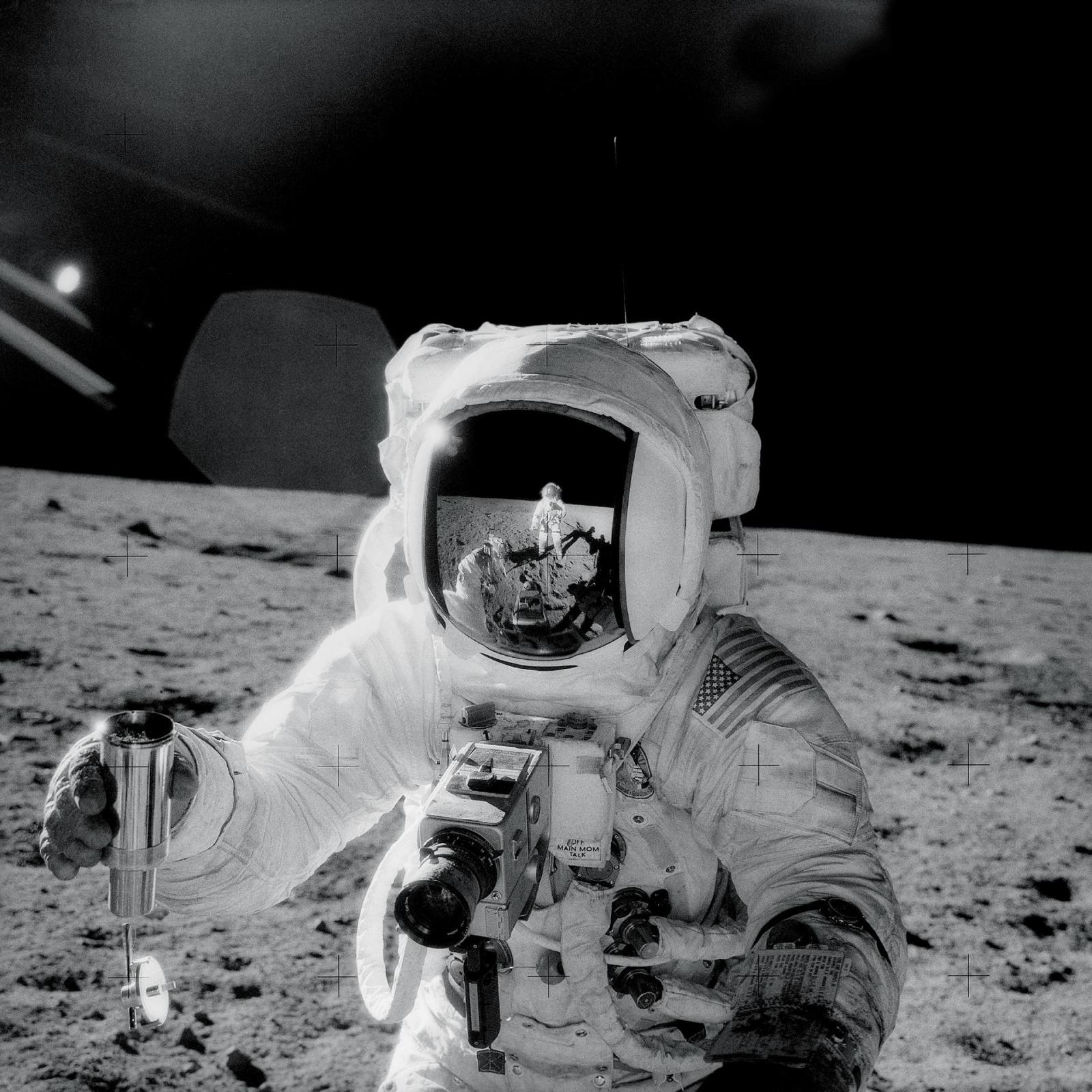 One of the astronauts on the Moon's surface is holding a container of lunar soil. The other astronaut is seen reflected in his helmet.