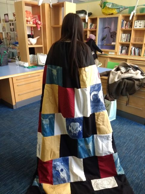 Photo of a student wearing a textile cape containing images of animal skulls
