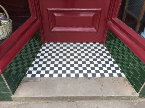 Image of threshold of Gwalia Stores at St Fagans national Museum of History. It is composed of alternating black and white squares.