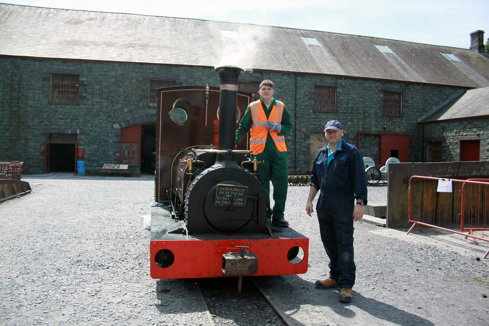 Two men standing by a steam train