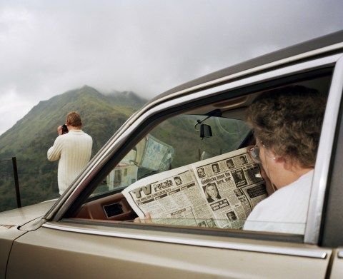 A photograph of a man looking out towards the mountains while a woman reads the paper in a car