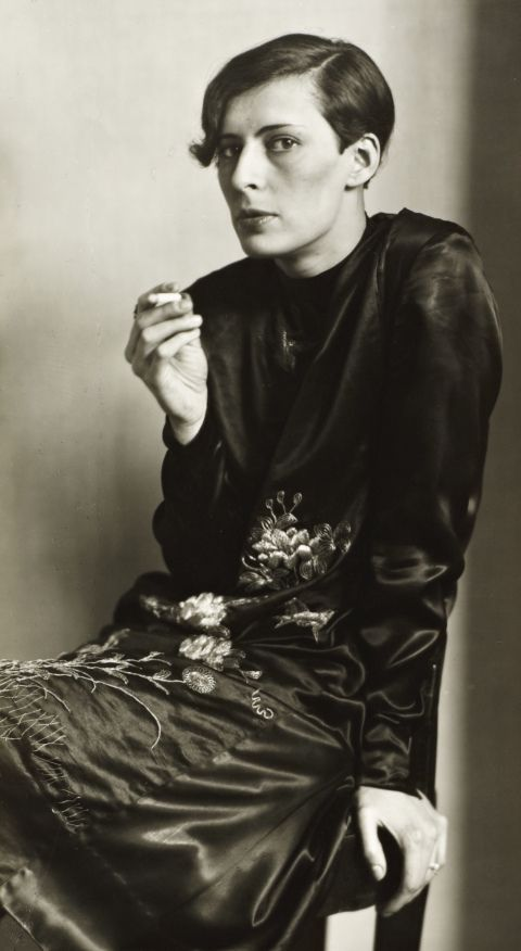 A black and white photo of a woman looking at the camera and smoking a cigarette