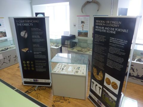 Objects in a small museum case, flanked by two pull-up banners.