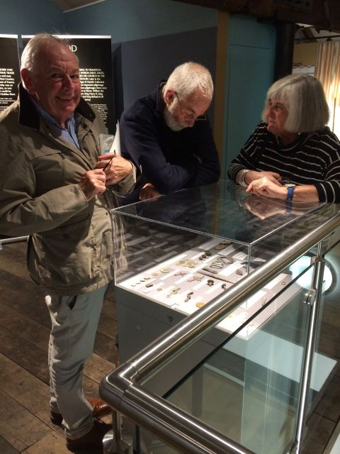 Three people are looking at objects in a display case.