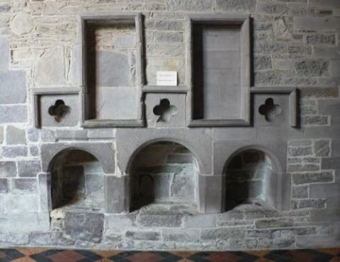 A picture of a stone wall in a cathedral with openings of vrious shapes and sizes.