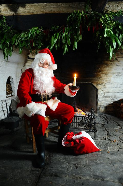 Father Christmas sat in front of the fire in Cilewent Farmhouse