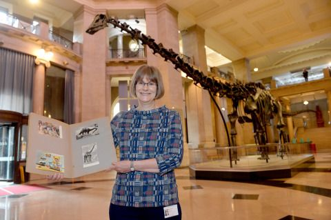 Dr Caroline Buttler with her scrapbook in National Museum Cardiff's main hall with Dippy in the background