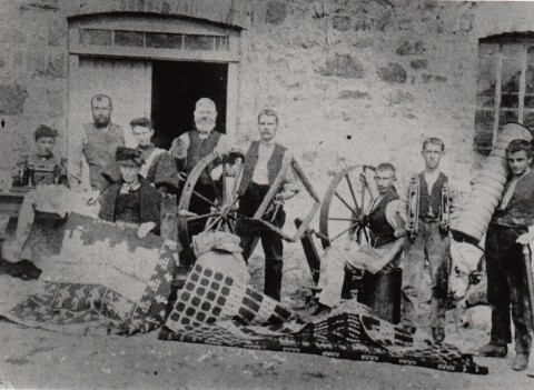 Black and white photograph showing nine workers outside Pwllheli Woollen Mill with blankets, spinning wheels and tools of their trade