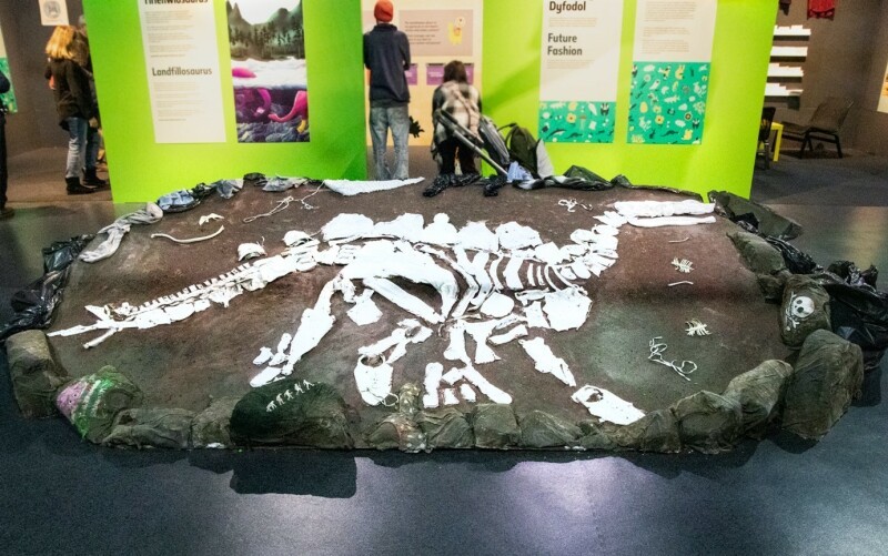 A photo of a display i the Dippy About nature exhibition. It shows a a model skeleton of a stegosaurus made from pieces of white clothing stuck to a large brown board.