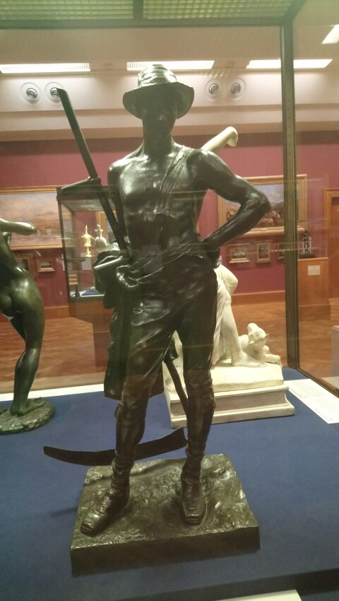 A bronze sculpture of a semi-nude male figure wearing a hat and holding a scythe