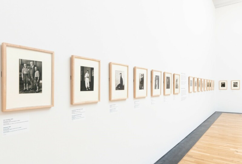 A photograph of the ARTIST ROOMS: August Sander exhibition, showing a series of square black and white portrait photographs in a line on a blank white wall