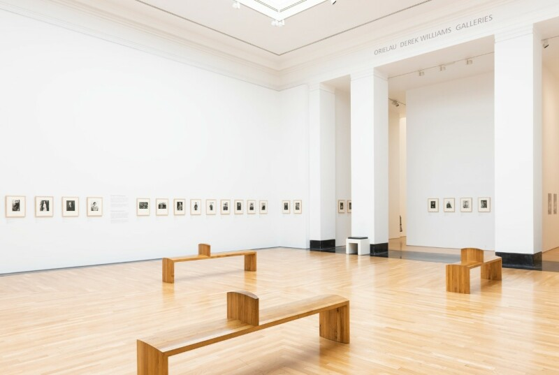 A photograph of the ARTIST ROOMS: August Sander exhibition, showing the entire gallery with small photos on the walls and wooden benches in the middle