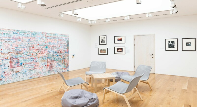 A photograph of the ARTIST ROOMS: August Sander exhibition, showing the visitor feedback section, with a graffiti comment wall, table and chairs and a bean bag