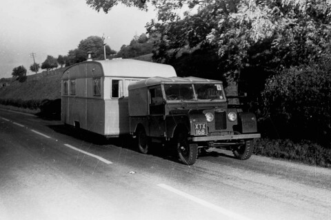 Black & white photograph of a Land Rover towing a caravan on a country road.