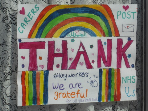 Hand-drawn rainbow on a piece of white paper on display in a house window. The sign is inscribed: 'THANK YOU KEY WORKERS We are grateful for all your hard work'.