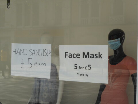 Shop window with two mannequins, one wearing a facemask. On the window, there are two signs - one advertising 5 facemaks for £5, the other hand-sanitiser for £5 each.
