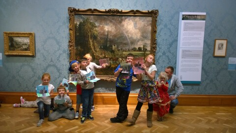 A group of young children standing in front of a painting, holding up their artworks