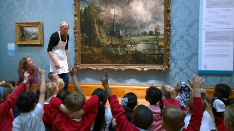 A group of school children sitting in an art gallery discussing Constable's painting with an artist