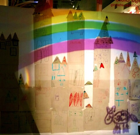 A cathedral drawn by school pupils on paper, with a rainbow projected over the top