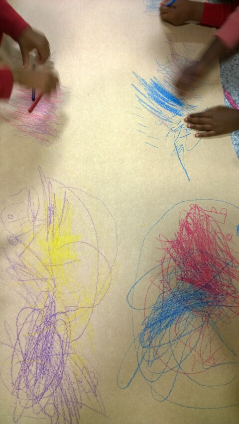 Children creating different marks with coloured pencils on a large sheet of paper