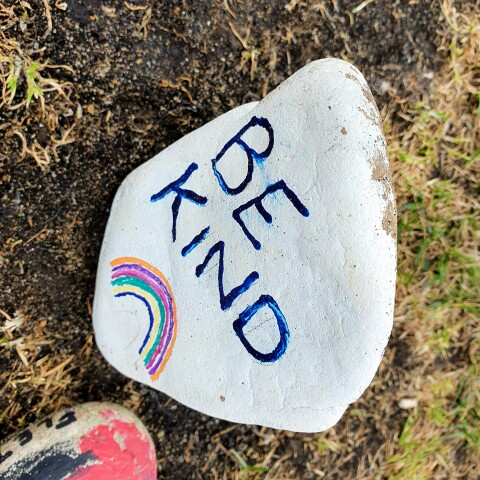 A small stone hand-painted with the words BE KIND and a rainbow