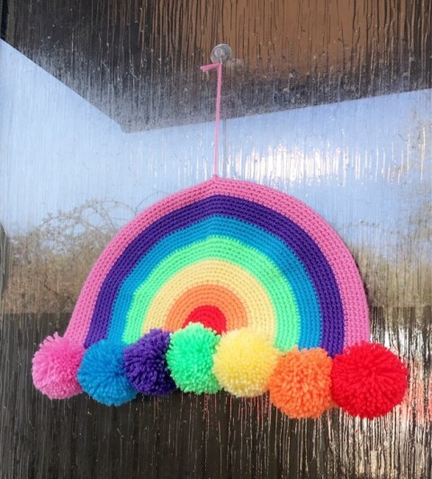 Colourful crocheted rainbow with pompoms displayed on a front door.