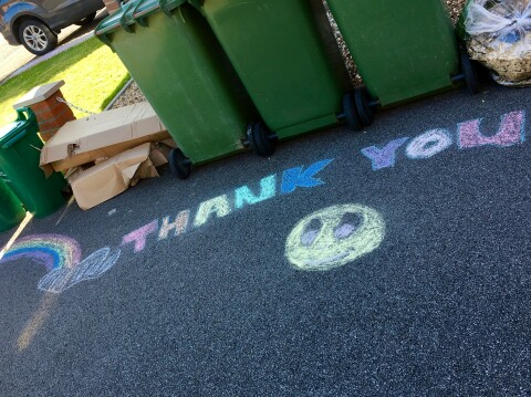 Chalk drawings and THANK YOU written on the floor in front of a row of bins