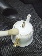 Cleaning a teapot using a brush
