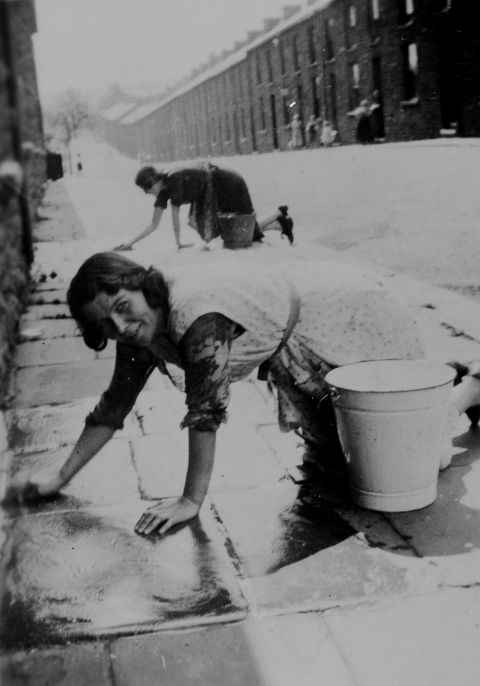Washing the pavement outside the front door, 1930s.