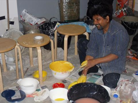 The artist Purnendu Dey mixing the natural powdered pigments with water